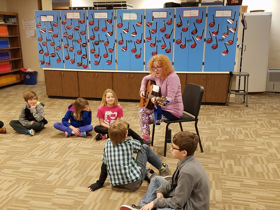 Picture of Debi Rogers playing guitar for students