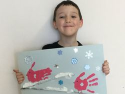 Picture of a student holding up his artwork of a winter scene