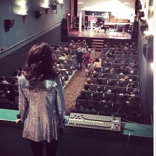 Picture of Lori Line on the Roxy Theater balcony overlooking the audience