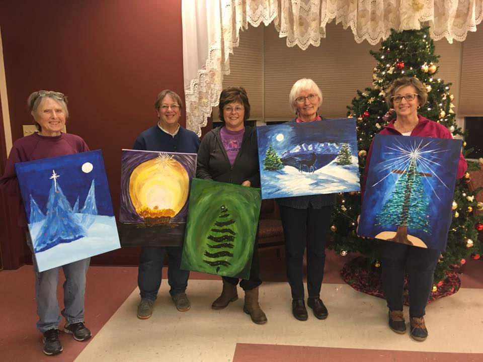 Picture of ladies holding up winter theme canvas paintings